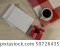 Gift box, notepad, textile and black coffee on wooden table 50726435