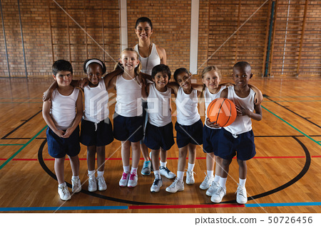 Happy schoolkids and female coach looking at camera at basketball court 50726456