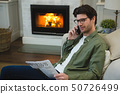 Man reading newspaper while talking on mobile phone 50726499
