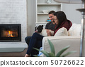 Couple relaxing with their pet dog in living room 50726622