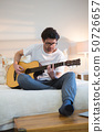 Man playing guitar in bedroom 50726657