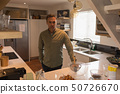 Man standing in kitchen at home 50726670