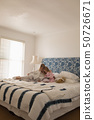 Mother with her daughter reading storybook in bedroom 50726671