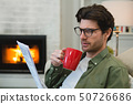 Man reading newspaper while having coffee in living room 50726686