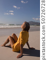 Young woman relaxing with eyes closed at beach 50726728