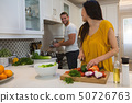 Woman cutting vegetables while man cooking food in kitchen 50726763