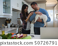 Couple playing with their pet dog in kitchen 50726791