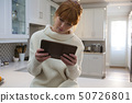 Woman using digital tablet in kitchen 50726801