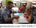 Young school teacher helping girl with study in classroom 50726817