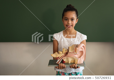 Front view of smiling asian schoolgirl holding anatomical model and looking at camera in classroom 50726931