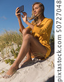 Woman taking selfie with mobile phone at beach 50727048