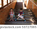 Schoolkids reading book while sitting on stairs of elementary school 50727065