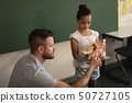 Male teacher explaining anatomical model to schoolgirl in classroom 50727105