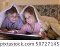 Siblings using digital tablet under blanket in bedroom 50727145