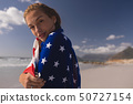 Young woman wrapped in American flag at beach 50727154