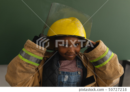 Front view of black schoolgirl with fire uniform looking at camera in classroom 50727218