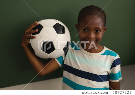 Front view of black schoolboy holding football and looking at camera in classroom 50727223