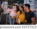 Friends taking selfie from mobile phone in food truck van 50727323
