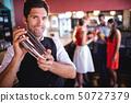 Bartender shaking cocktail mixer in nightclub 50727379