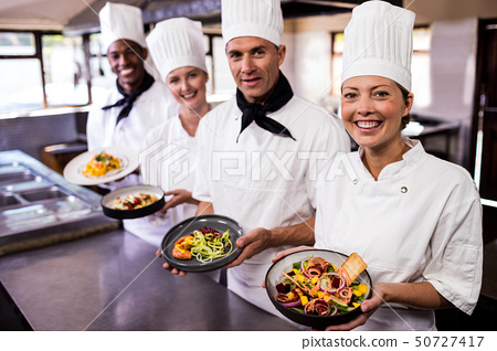 Group of chefs holding plate of prepared food in kitchen 50727417