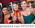 Female friends enjoying wine in night club 50727447