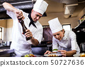 Male and female chefs preparing food in kitchen 50727636