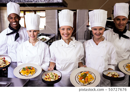 Group of chefs holding plate of prepared pasta in kitchen 50727676