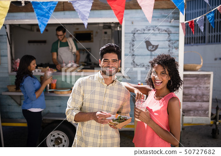 Smiling couple standing with snacks and juice 50727682