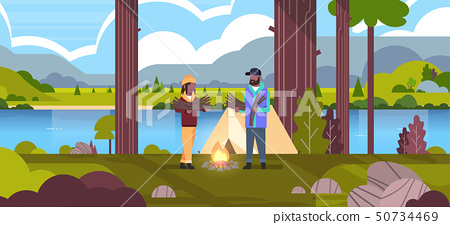 couple tourists hikers holding firewood african american man woman organizing fire near camp tent 50734469
