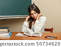 Beautiful young woman with glasses reading a book 50734620