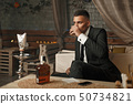 Handsome young man in a suit drinking whiskey  50734821