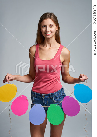 Smiling woman holding garland of Easter eggs shape 50736848