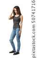 Fit young woman in gray sleeveless top and blue jeans standing in half-turn with troubled look on 50741716