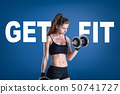 Young athletic girl in black sportswear with a dumbbell and GET FIT sign on blue background 50741727