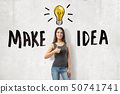 Young brunette girl wearing casual jeans and t-shirt showing thumb up with MAKE IDEA sign and 50741741