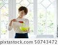 Woman housewife cooking salad 50743472