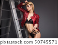 Spectacular blonde in underwear and leather burgundy jacket in the studio on a gray background. 50745571