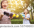happy little girls playing water guns in the park 50749003
