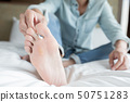 applying cream for athletes foot 50751283