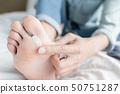 applying cream for athletes foot 50751287