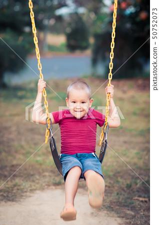 Little boy swinging on a swing 50752073