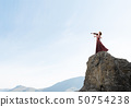 Woman violinist in red dress playing melody against cloudy sky 50754238