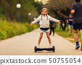 Beautiful little girl riding the GyroScooter in the park 50755054