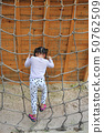 Rear view little kid girl at playground rope net. 50762509