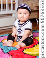 A pretty baby in a striped shirt and hats seated on the mat in the room 50763563