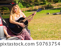 Hippie woman playing guitar in van car 50763754