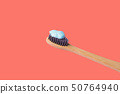 Toothbrush with blue toothpaste on pink coral 50764940