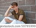 Handsome man with hair sitting near a brick wall 50765999