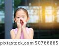 Little girl shouting through hands like megaphone. 50766865