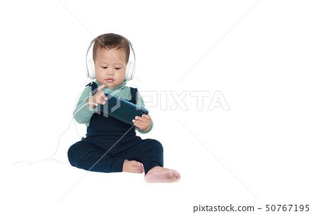 Little boy enjoys listening music by headphones. 50767195